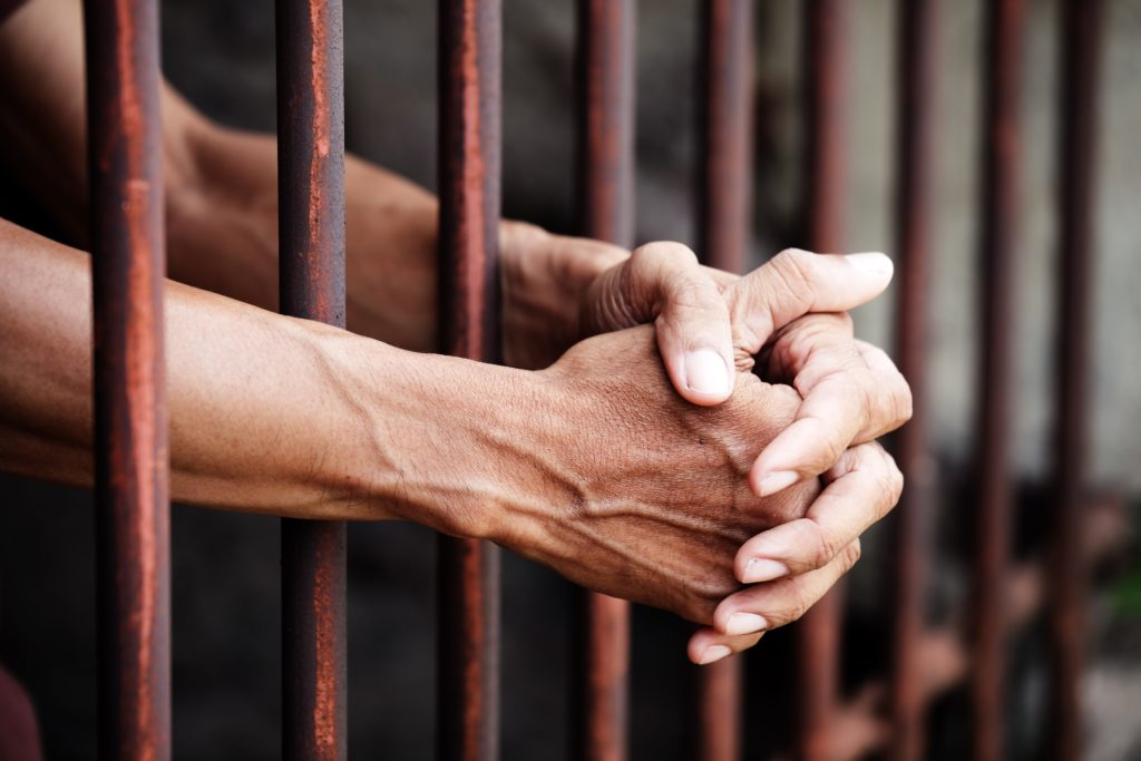 Hands of prisoner in jail.