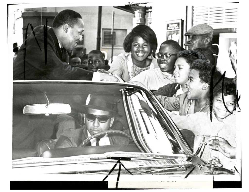 Dr. Martin Luther King, Jr. leaning out of a car and shaking kids' hands.